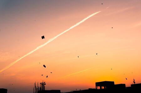 Kites flying at sunset in Jaipur against teh silhouette of buildings. This is in celebration of Makar Sankranti or Uttarayan