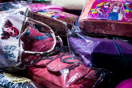 Pile of colorful, low budget purses for ladies. These are popular items at the cutting edge of fashion