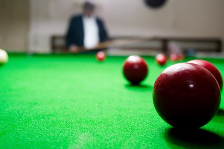 Man in suit watching the table in a billiards pool game