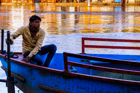 Delhi, India - 05th Mar 2017: Indian boatsman sitting on a boat waiting for passengers. These simple open boats ply most indian rivers