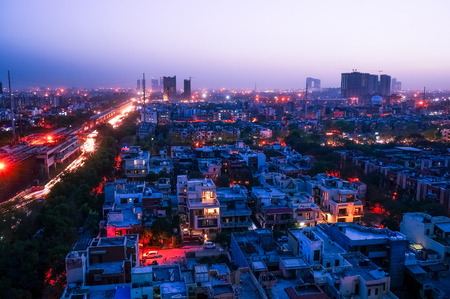 Noida cityscape at night with lights on the buildings and the construction cranes clearly visible