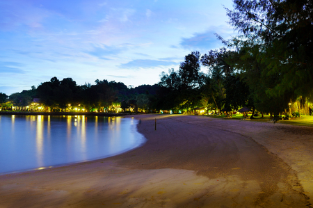Sandy beach at night with lights, houses, and trees visible in teh distance. The blue evening sky give an overall holiday vacation feel Stock Photo