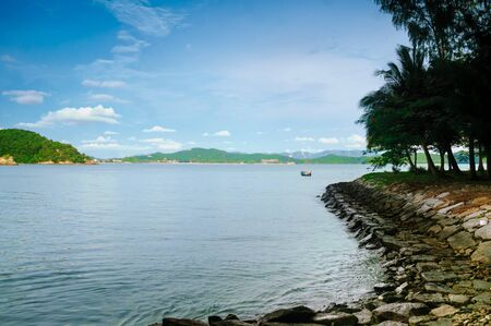 beautiful seaside walkway with trees dotting it. The blue cloudy sky and mountains add to the image of Langkawi Malaysia