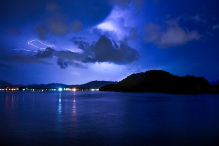 Lightning over a calm sea, dark clouds and an island. Distant lights form a city are also visible in this night shot Stock Photo