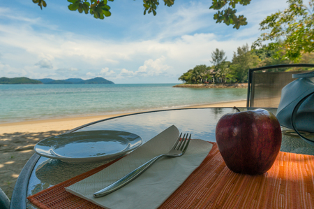 Table on the beach with cutlery and an apple