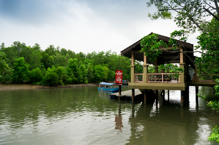Boat docking against wooden cabin with a sign in Malay