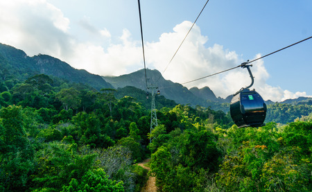 Ropeway with cab going towards green hills and cloudy skies