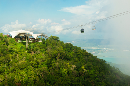 Cable car station atop tree covered mountain with leaving cab Stock Photo