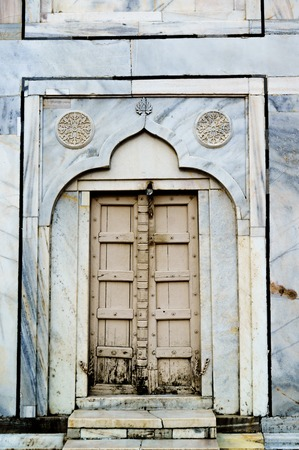 Old wooden door set in marble wall with designs Stock Photo