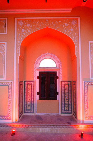 Arched window in a pink sandstone wall in Jaipur