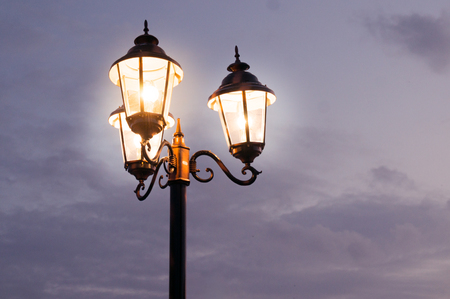 Old fashioned street lights shot against a cloudy sky