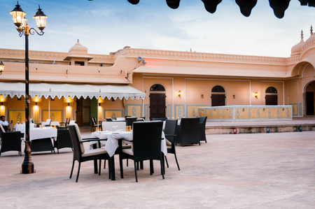 Elegant eating space with dining tables, wooden chairs and beautiful lights placed inside the courtyard of a Rajasthani fort. The cloudy sky and ancient walls make this a romantic place for a dinner date Stock Photo