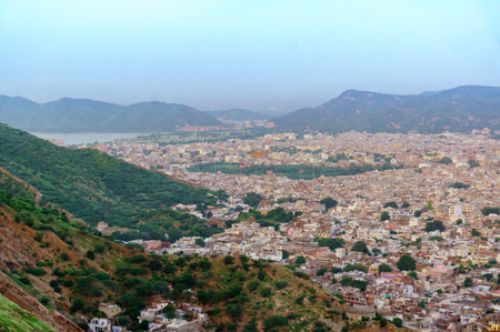 Cityscape of Jaipur city with the bordering Aravali hills and the city of Amber at the base. The cloudy sky and mountains in the background add to the beauty of the place Stock Photo