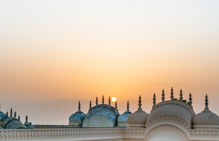 Domes and spires of the Nahargarh fort in Jaipur shot against the setting sun. The hindu Rajput architecture is complemented perfectly by the orange hue of the sun Stock Photo