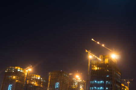 Under construction sky scraper with cranes, working lights shot against a moonlit cloudy sky. One of the number of projects that have started in Gurgaon, Noida, Delhi, Hyderabad, Bangalore real estate market