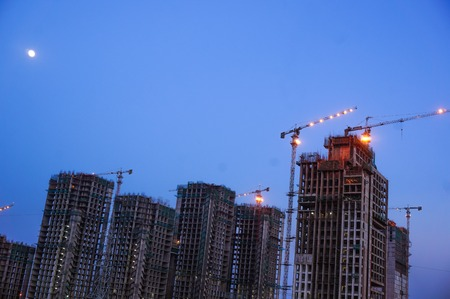 Under construction building with cranes, supports and other construction equipment. Shot against the twilight sky in a major city like Gurgaon, Delhi, Noida, Hyderabad. Stock Photo