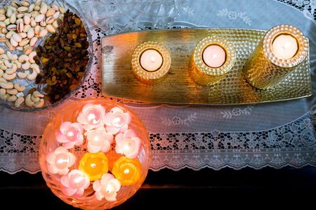 Flatlay shot of floating candles, golden candles and dry fruits Stock Photo
