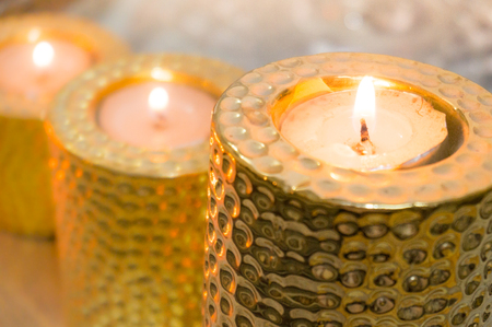 Beautiful golden candle holders with tea lights placed on them. Perfect for home office decoration with scented candles