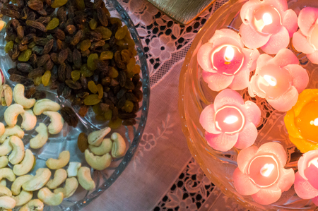 Glass bowl filled with flower shaped floating candles and a glass try with dry fruits like cashew nuts, raisins. This is the traditional decoration and food served during winter festivals in india