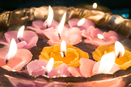 Beautiful floating candles lit and floating on a glass bowl of water. These are traditional decorations during holidays like diwali christmas, thanksgiving.