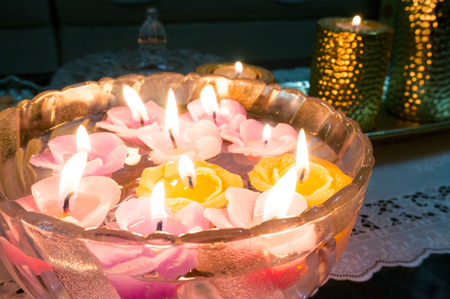 Glass bowl filled with floating candles shaped like colorful flowers. Perfect for home decoration during celebrations
