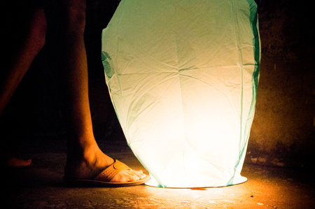 Boy holding down green paper lantern using sandled feet. Chinese lanters have become a tradition of makar sankranti and diwali