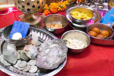 Hindu ceremony with sweets, coins, god, silver wortshipping the