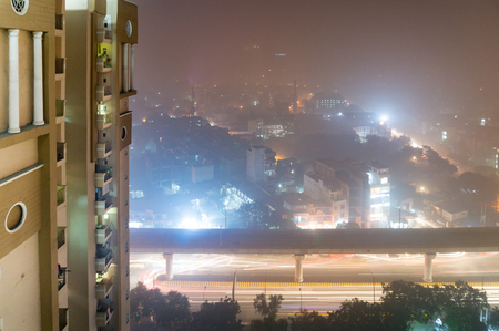 Shot of building on a foggy night in delhi, Noida, Gurgaon. The heavy toxic smog gives a bright glow to the lights of the homes and offices in the distance Stock Photo