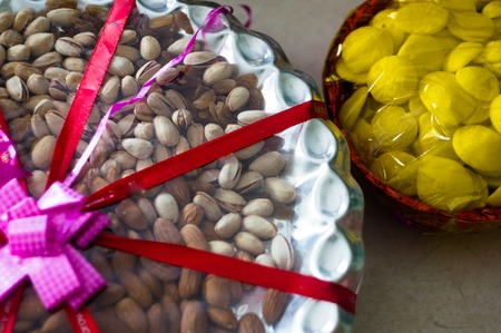 dry fruits and sweets packed in basket with ribbons