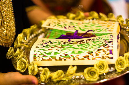 Handmade traditional invitation card being carried on a golden tray decorated with flowers being taken to the groom