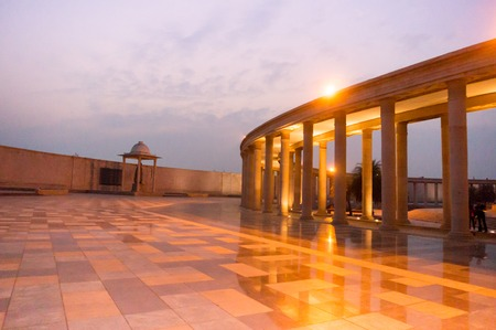 Walkway with a roof supported by pillars in a courtyard. The lights and purple blue sky of dusk make this shot of the Ambedkar Park.
