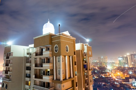 Skyscaper shot against the noida cityscape on cloudy night Stock Photo