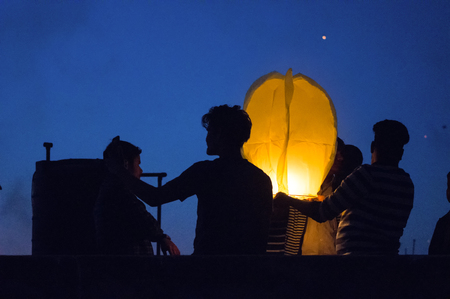 Silhouette of people flying a sky lantern during dusk
