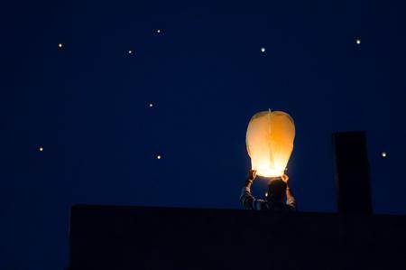 Silhouette of man flying paper sky lantern shot against a sky fi