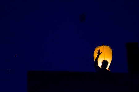 Silhouette of man flying a paper sky lantern at dusk