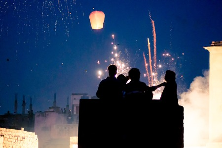 Silhouette of people standing in front of fireworks and sky lant