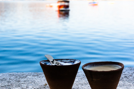 Tea and coffee in earthenware pots on a lakeside