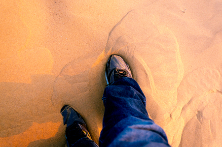 Man wearing running shoes in the sand