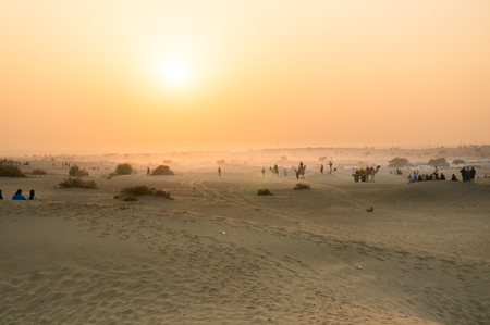 Foggy sunset in thar desert with camels on horizon Stock Photo