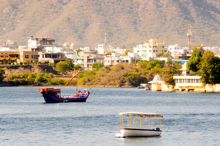 Boats on lake pichola with the city of Udaipur in the background