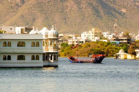 Ornate boat passing near a palace on a lake