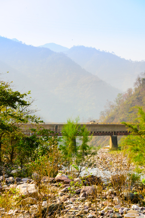 Vertical shot of mountains, bridge and dry riverbed