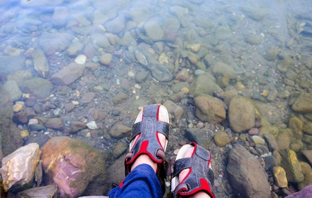 Feet with fasionable sandles placed above the clear water of a c
