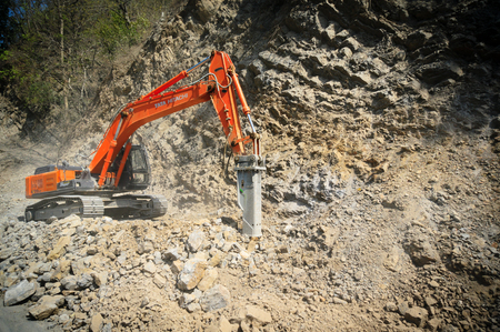 Construction excavator clearing up rocks from a landslide Éditoriale