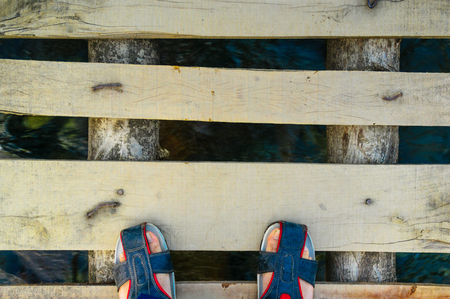 Feet in fashionable sandles on wooden bridge with water flowing