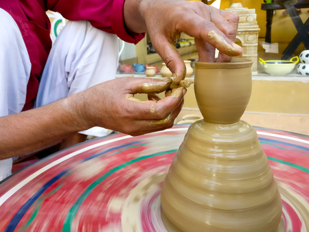 Potter making clay pot on a colorful wheel Stock Photo