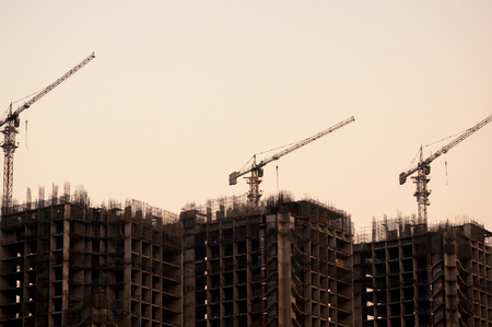 3 under construction buildings with cranes shot at dusk