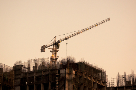 crane on top of an under construction building at dusk