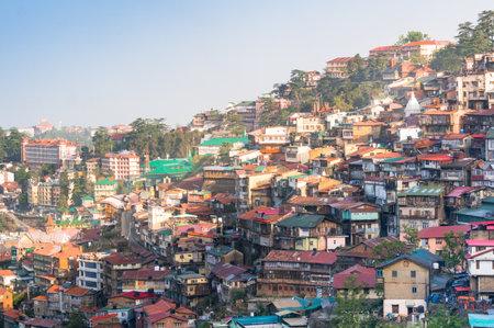 buildings on a mountainside of shimla at dusk