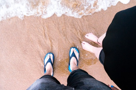 downward looking shot of couple standing on a beach with waves c